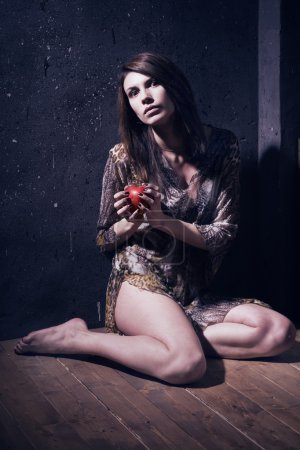 Photo for Asylum. Lonely mad woman with red apple sitting on a floor. Low key. - Royalty Free Image