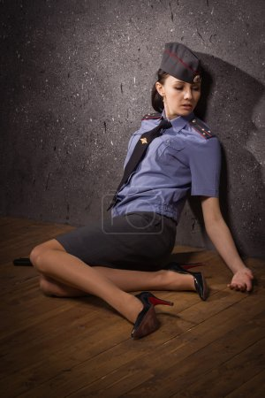 Photo for Crime scene imitation. Woman police officer lying on a floor - Royalty Free Image