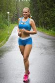 Šťastná dívka běží v zeleném parku na deštivé letní den