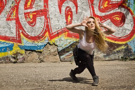 Young girl dancing on graffiti background