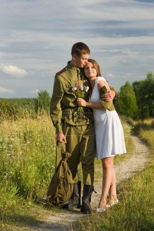 Photo pour Une fille heureuse rencontre un soldat. Retour du soldat soviétique en uniforme de la Seconde Guerre mondiale - image libre de droit