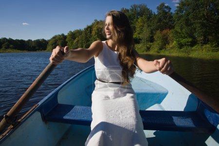 Girl rowing oars in the boat