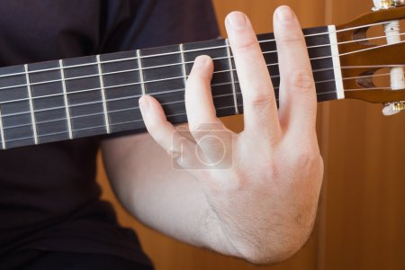 Close up of guitarist hand playing acoustic guita...