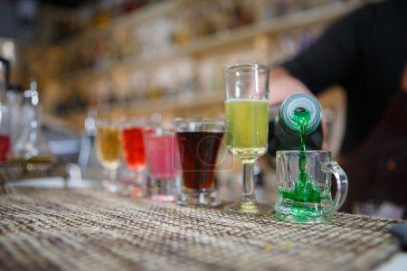 Photo pour Barman verse diverses boissons alcoolisées dans de petits verres sur le bar - image libre de droit