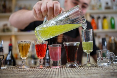 Photo for Bartender pours various of alcohol drink into small glasses on bar - Royalty Free Image