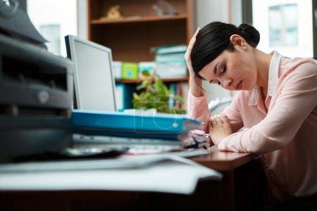 Tired businesswoman sleeping on the desk.