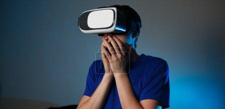 Photo pour Homme portant des lunettes de réalité virtuelle à la maison. Concept VR avec émotions . - image libre de droit