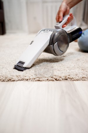 Female hand holding small cordless vacuum cleaner and cleaning rug