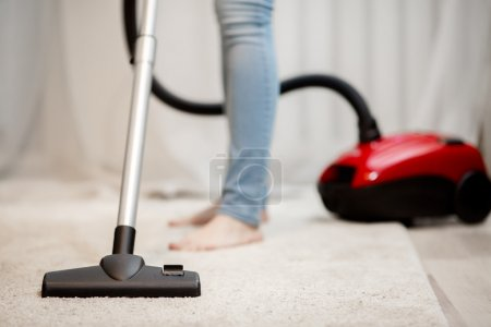 Femme faisant le nettoyage de la maison, aspirant tapis avec pile épaisse