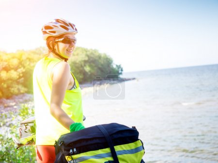 Young woman with bicycle standing on seaside