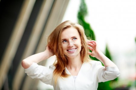Young woman touches her hair.