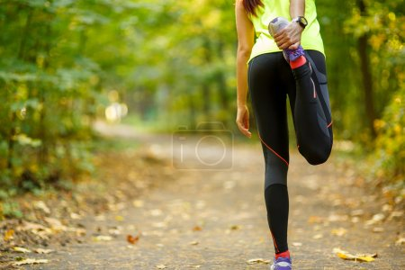 Photo for Young woman exercising and stretching muscles before sport activity in park - Royalty Free Image