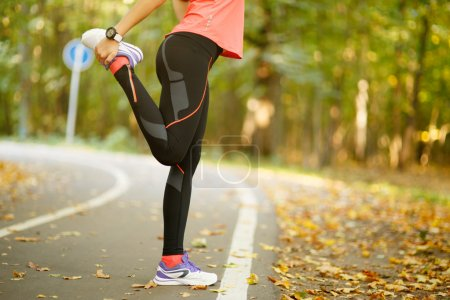 Photo for Detail of woman stretching legs before jogging in autumn nature - Royalty Free Image