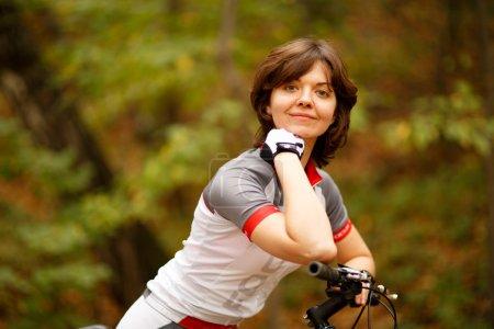 Photo pour Virée vélo équitation femme sur le chemin d'accès au parc plein d'arbres - image libre de droit