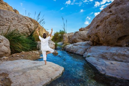 woman practices yoga on small lake