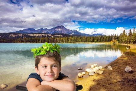 boy in carnival wreath on the lake