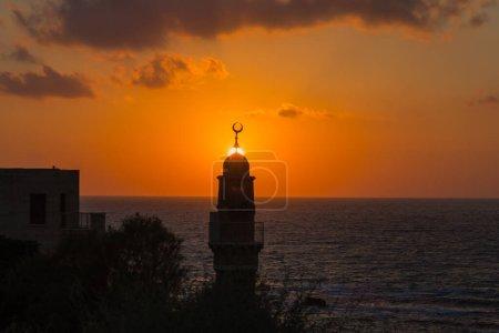 Photo pour Tour ronde couronnée d'un croissant est un minaret musulman. Le soleil couchant plonge dans la mer Méditerranée. Vieux Yaffo, Tel Aviv. Concept actif, informatif et photo du tourisme - image libre de droit