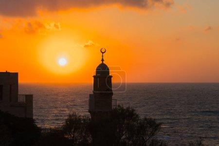 Photo pour Tour ronde couronnée d'un croissant est un minaret musulman. Old Yaffo - une des villes les plus anciennes du monde. Le soleil plonge dans la mer Méditerranée. Concept actif et photo du tourisme - image libre de droit