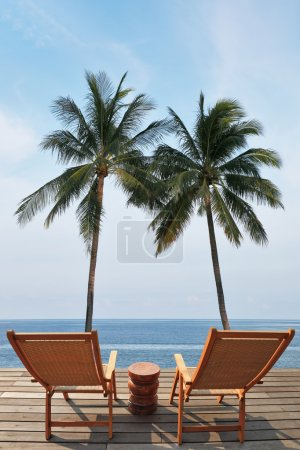 Photo pour Two convenient comfortable guest sun loungers and a bedside table are worth on a wooden platform. Great review for a luxury beachfront pool, the ocean and swaying palm trees. Charming lookout for two - image libre de droit
