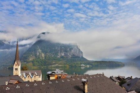 Photo pour Clocher mince et l'église sur la rive du lac Hallstatt dans une petite ville en Autriche - image libre de droit