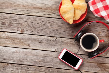 Fresh croissants, coffee, smartphone and headphones