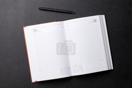 Photo for Office leather table with notepad and pen on it. Top view with copy space - Royalty Free Image