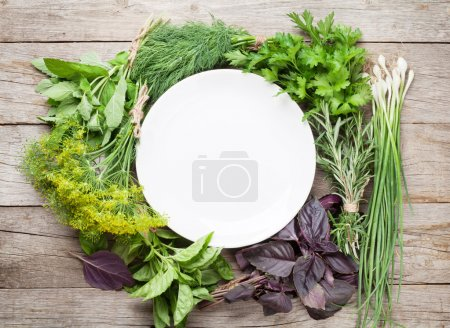 Photo for Fresh garden herbs and empty plate on wooden table. Top view - Royalty Free Image