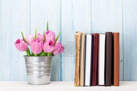 Photo pour Bouquet de tulipes roses fraîches et livres sur étagère devant un mur de pierre - image libre de droit