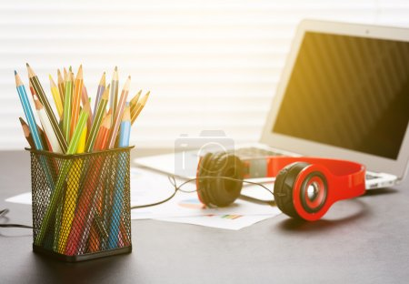 Photo for Office workplace with with laptop, reports, headphones and pencils on wooden desk table in front of window with blinds. Sunset light - Royalty Free Image