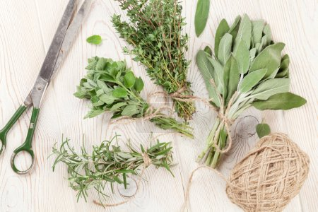 Photo for Fresh garden herbs on wooden table. Oregano, thyme, sage, rosemary. Top view - Royalty Free Image