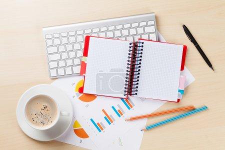 Foto de Escritorio de oficina con gráficos, taza de café, PC y bloc de notas en la mesa de madera. Vista superior con espacio de copia - Imagen libre de derechos