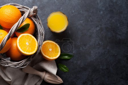 Photo for Fresh orange fruits and juice on stone table. Top view with copy space - Royalty Free Image