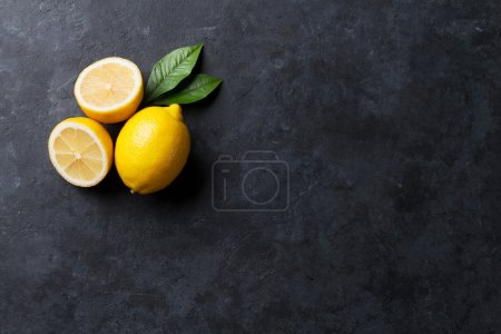 Photo for Fresh ripe lemons on dark stone background. Top view with copy space - Royalty Free Image
