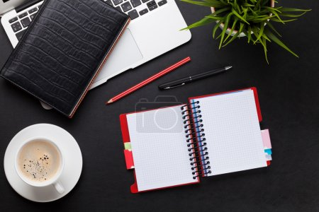 Foto de Mesa de escritorio de oficina de cuero con portátil, taza de café, bloc de notas y planta. Vista superior con espacio de copia - Imagen libre de derechos