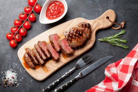 Photo for Grilled striploin sliced steak on cutting board over stone table. Top view - Royalty Free Image