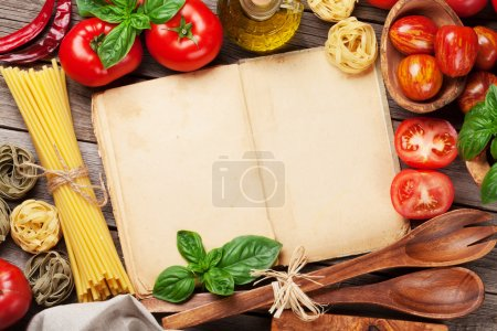 Photo for Italian food cooking. Tomatoes, basil, spaghetti pasta, olive oil and cookbook for your recipe on wooden kitchen table. Top view with copy space - Royalty Free Image