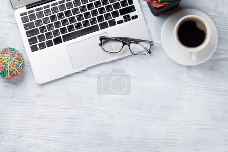 Desk table with laptop, coffee and glasses