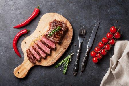 Photo pour Steak de bœuf tranché grillé sur planche à découper sur table en pierre. Vue du dessus - image libre de droit