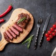 Grilled sliced beef steak on cutting board over st...