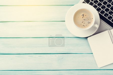 Photo for Desk table with laptop, coffee and notepad on wooden table with sun beam. Workplace. Top view with copy space. - Royalty Free Image