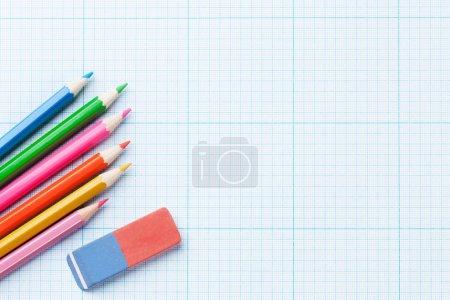 Photo pour Crayons colorés sur papier ligné millimètre. Vue supérieure avec espace de copie - image libre de droit