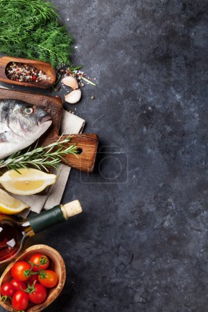 Photo for Raw fish cooking and ingredients. White wine, dorado, lemon, herbs and spices. Top view with copy space on stone table - Royalty Free Image