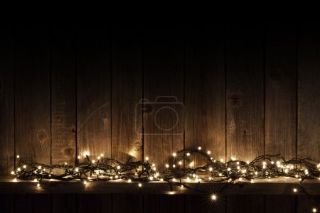 Photo for Yellow Christmas lights on wooden wall background - Royalty Free Image