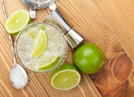 Photo for Classic margarita cocktail with salty rim on wooden table with limes and drink utensils - Royalty Free Image