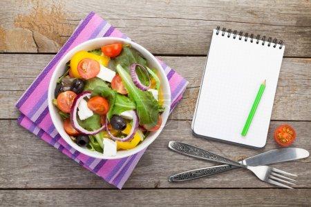 Fresh healthy salad and notepad