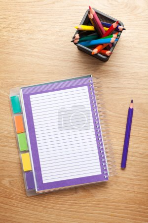 Office table with blank notepad and colorful pencils
