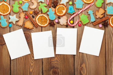Photo for Christmas wooden background with photo frames, candies, spices and gingerbread cookies - Royalty Free Image