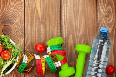 Dumbbells, tape measure and healthy food over wood...