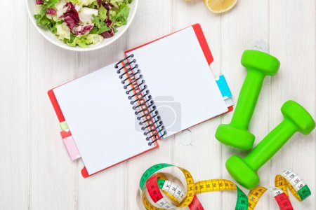 Dumbells, tape measure, healthy food and notepad for copy space
