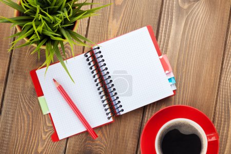 Office table with flower, blank notepad and coffee cup